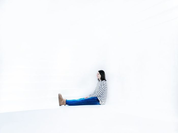 Side view of woman sitting against white background