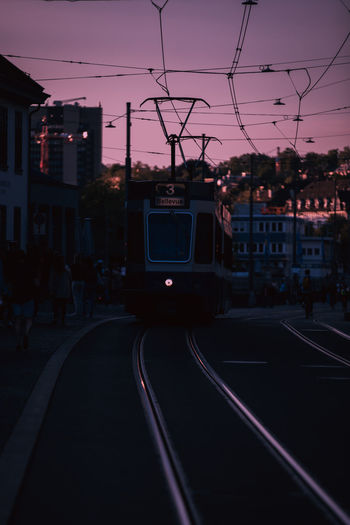 View of railroad tracks in city at sunset