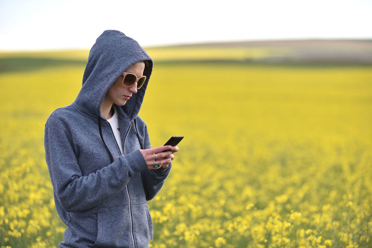 Close-Up Of Woman Holding Phone While Standing On Field