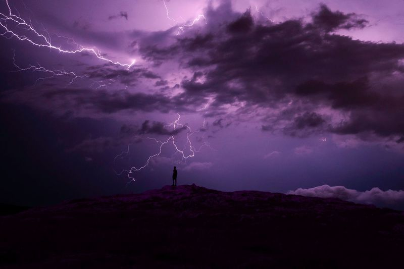 Silhouette man standing on mountain against thunderstorm
