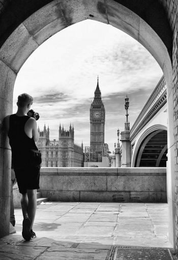 Rear View Full Length Of Man Photographing Big Ben While Standing At Archway In City