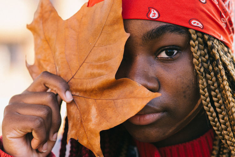 Portrait of a black girl with colored braids covering her eye with a tree leaf. autumn time.