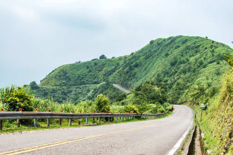 Road Transportation Sky Mountain Tree Plant Nature Day Green Color Direction Beauty In Nature Scenics - Nature Tranquility The Way Forward No People Non-urban Scene Symbol Land Tranquil Scene Sign Mountain Road Winding Road Outdoors Crash Barrier