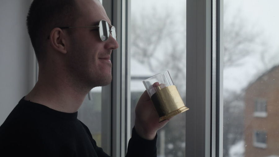Portrait of young man drinking glass window