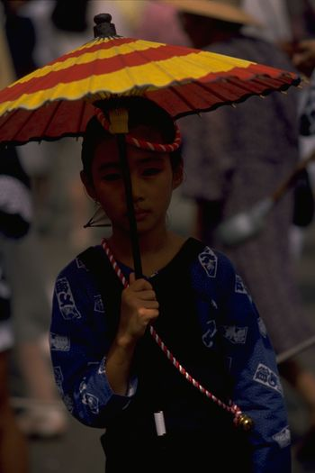 "Japanese girl in traditional dress during a festival in Kumamoto, Japan. From Nomadic Gatherings - http://tnot.es/Nomadic Every 15th September the citizens of Kumamoto celebrate the Zuibyo Festival; the festival of Fujisaki Hachiman Shrine. The street processions continued all day and well after sunset. To the rhythmic beat of skinned drums and cymbals, whistles and chants, groups of costumed Samurai men, women, and children paraded their colours, twirled parasols and wafted traditional fans. Each group had a horse at the front and a float-cum-shrine at the rear. The larger men led the horse, continually trying to startle and provoke the animal into bucking near the gathered crowd, while at the same time backing-off the crowd to add to the drama. The float housed the megaphoned cheer-leader, closely followed by the rhythm beaters and performing clan. Equally essential in the late summer heat, refreshments were stored behind the decorative facade. As a foreigner interested in photographing the colourful pageant, I became a focus of attention myself. Attractive young women shyly smiled from behind their fans; sweaty Samurai ceremonially bowed; and younger boys enthusiastically shook my hand, patted my shoulder or simply asked: ""How are you?"" When I wasn't working the lens and shutter release, an odd can of beer was thrust into my hand. Very grateful I was too. http://pics.travelnotes.org/ Fujisaki Hachiman Shrine Japan Japanese  Michel Guntern Travel Photography Candid Childhood Clothing Day Festival Front View Girl Japanese Girl Kumamoto Lifestyles One Person Outdoors Parasol People Portrait Real People Standing Sun And Shade Traditional Dress Travelpics"