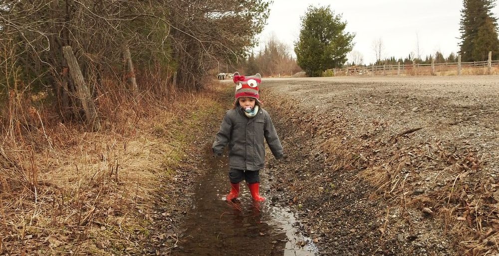 """"""" She Loves The Springtime """" * * * Water Puddles Child Child Activities Child In Water Puddle Child Wearing Rubber Boots Childhood Children Having Fun Outside Country Life Country Walks Cute Child Ditch Water Leisure Activity Outdoors Rubber Boots And Mud Springtime Warm Clothing"""