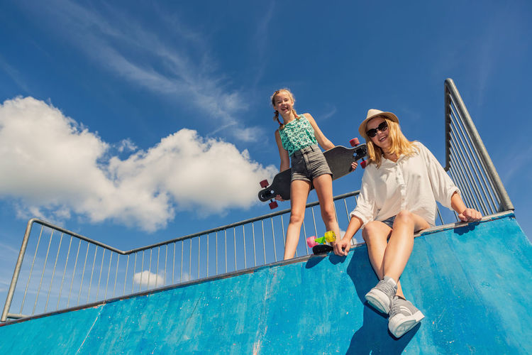 Low angle portrait of siblings at skateboard park
