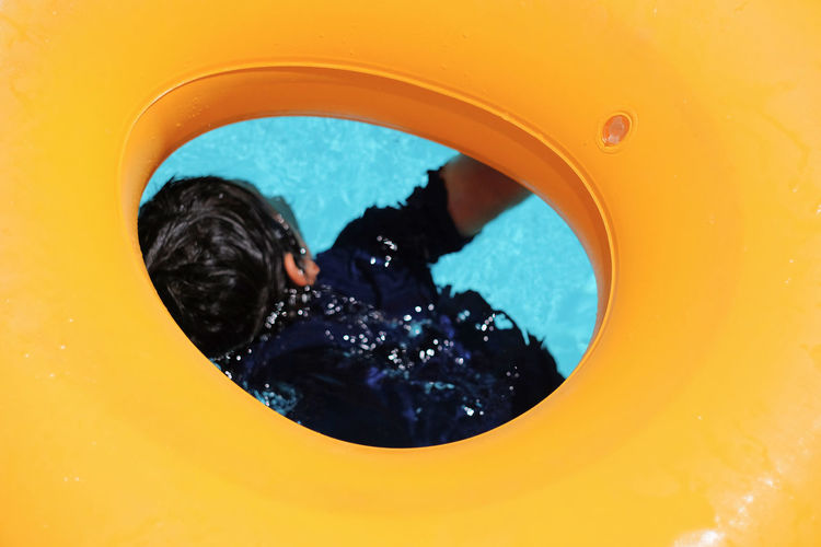 6 years old boy underwater in a pool, seen through yellow buoy 6 Years Old California FUJIFILM X-T1 Learning To Swim Swimming USA Boy Buoy Childhood Close-up Danger Day Drawning Floating One Person Swimming Pool Underwater Vintage Lens Water Yellow