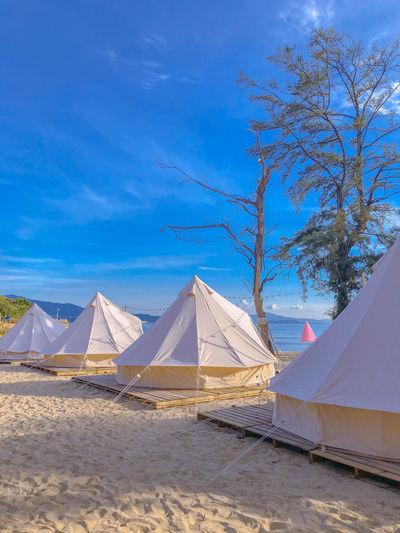 Tent on beach against blue sky