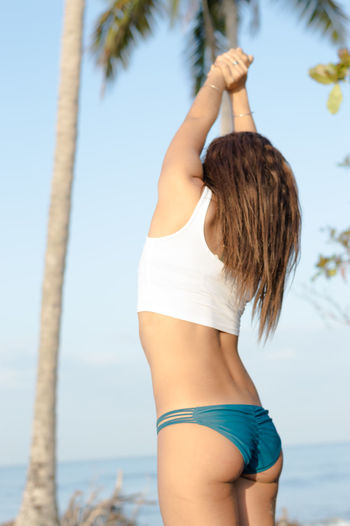 Midsection of woman standing at beach against sky