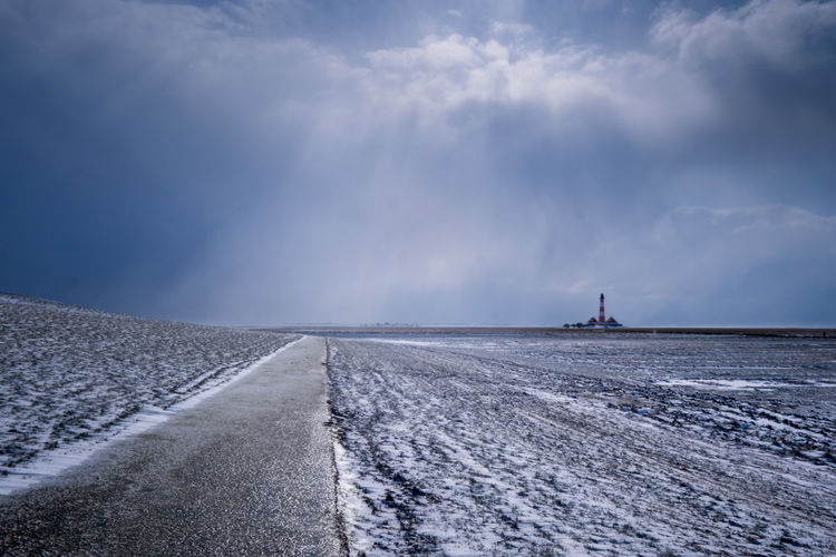 Road Amidst Snow Covered Landscape Against Sky