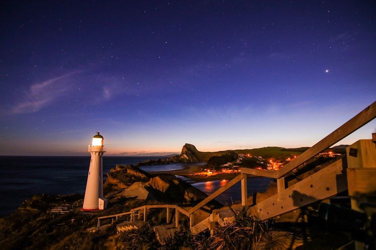 Lighthouse by sea against clear blue sky at night