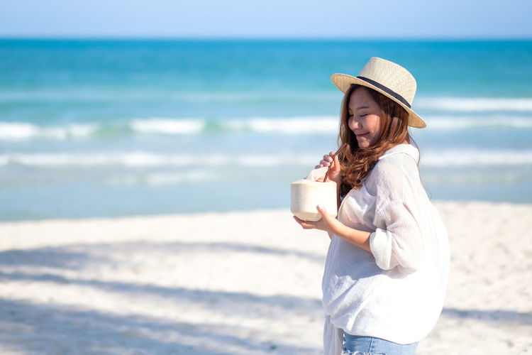 Portrait image of a beautiful asian woman holding and drinking coconut juice on the beach Stunning Smile Sky Seashore Sea Relax Portrait People Paradise Outdoor Ocean Nature Looking Lifestyle Life Leisure Landscape Island Holiday Holding Hat Happy Happiness Hair Girl Female Fashion Enjoy Drink Day Coconut Blue Beauty Beautiful Beach Background Back Asian  Adult