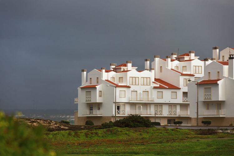Residential buildings by sea against sky