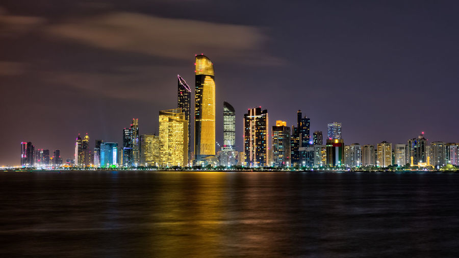 Illuminated modern buildings by sea against sky at night