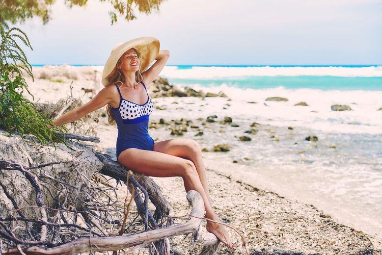Mid Adult Woman In Swimwear Posing At Beach
