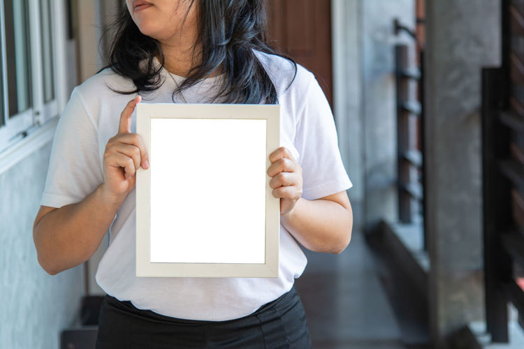 Midsection of woman standing against white wall