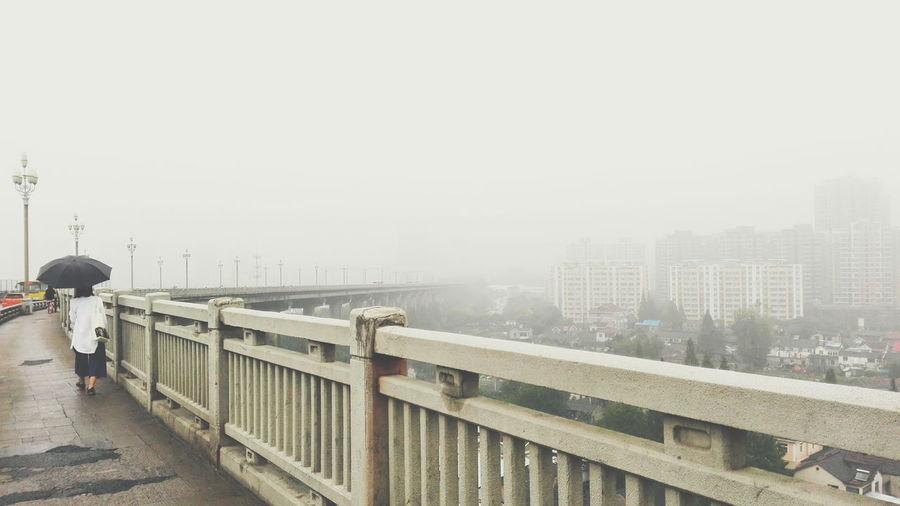 Rear view of woman walking with umbrella on nanjing yangtze river bridge