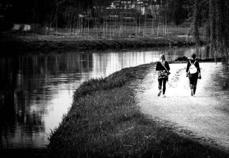Rear view of people walking on lake