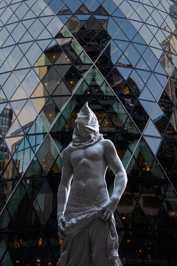 Low angle view of statue against modern building
