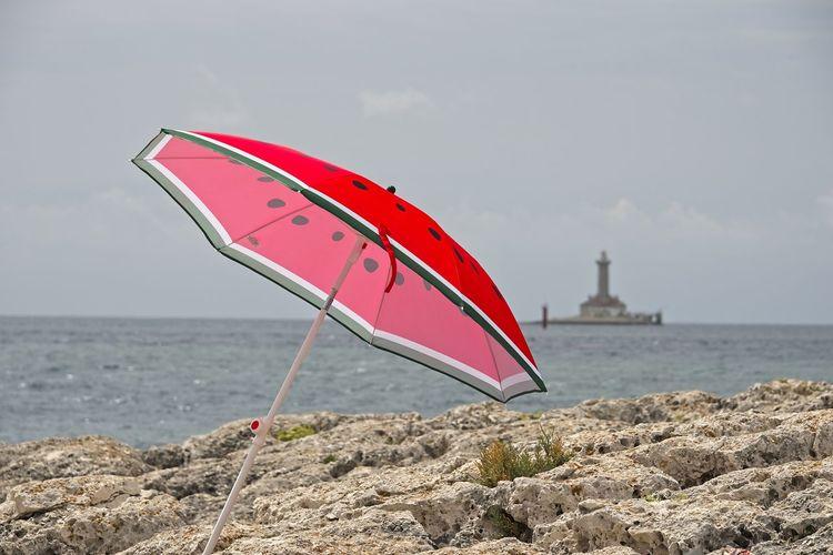 Red umbrella on beach against sky