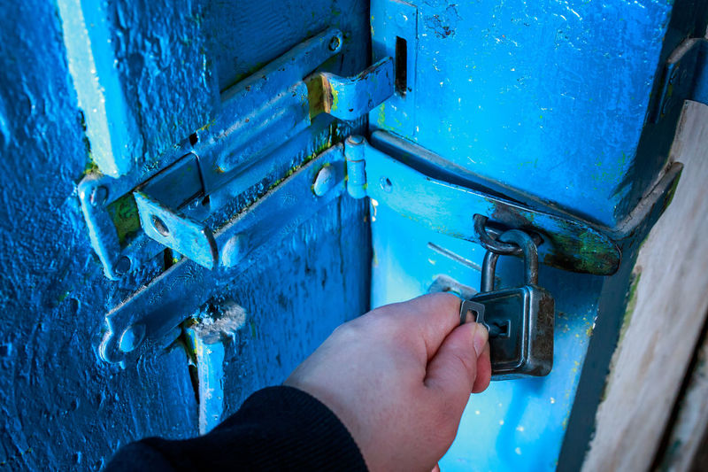 Cropped hand opening padlock with key