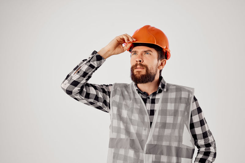 Man looking away while standing against gray background
