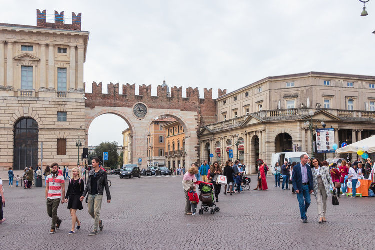 Verona, Italy - September 26, 2015 : Tourists walking around the Piazza Bra square on a cloudy day, inspect the I portoni della Bra Gate and the square in Verona, Italy. Europe Ancient Architecture Art Building Center City Culture Day Famous Heritage Historic House Italy Landmark Old Outdoors People Time Tourism Tourist Travel Verona Walking World