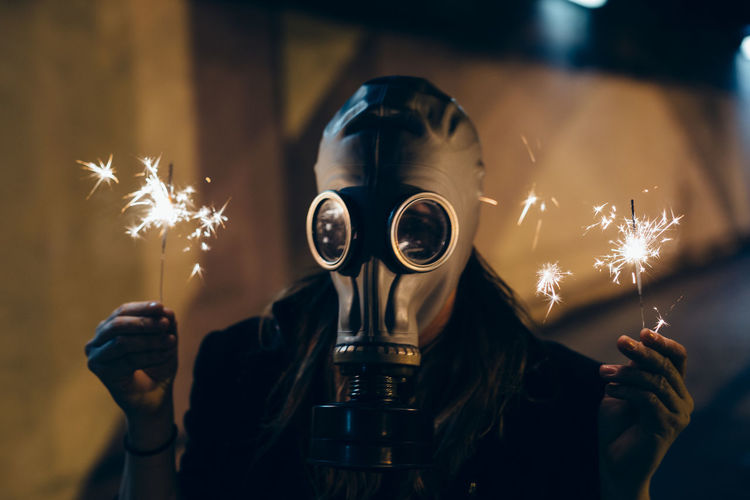 Woman holding illuminated sparklers while wearing gas mask