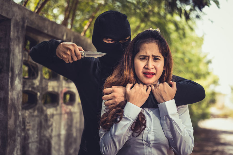 Fight Force Gun Knife Man Woman Abuse Day Front View Hostage Leisure Activity Lifestyles Lock Outdoors Real People Robber Standing Submission Terrorist Thief Togetherness Two People Weapon Young Adult Young Women