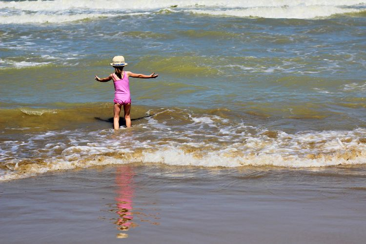 Beach Casual Clothing Child Childhood Day Full Length Girls Land Leisure Activity Lifestyles Motion One Person Outdoors Real People Rear View Sea Standing Water Wave