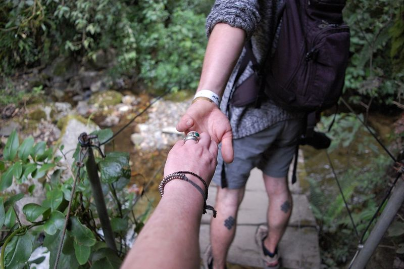 Cropped image of woman holding man hand on footpath