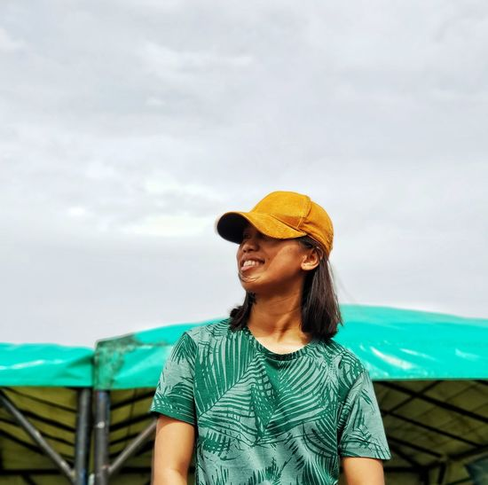 Smiling young woman wearing cap while standing against sky