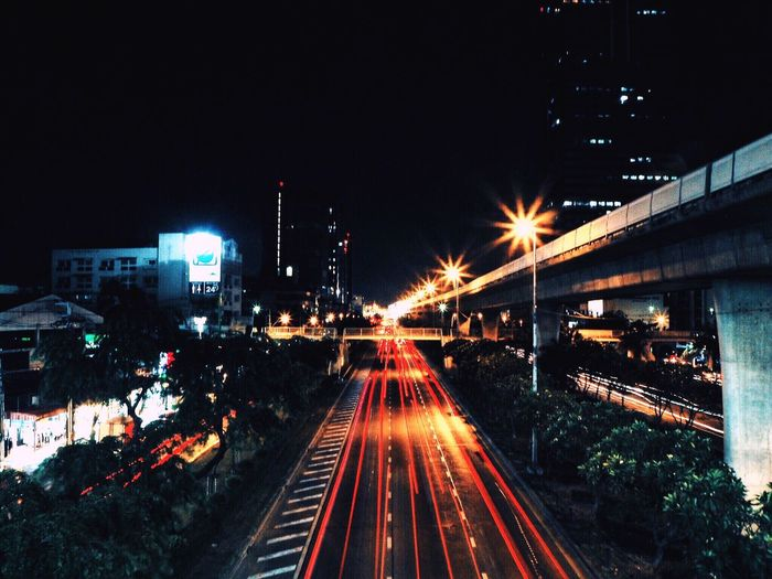High angle view of light trails on road by bridge in city at night