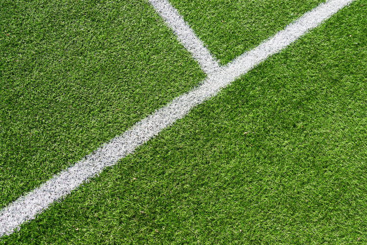 Green artificial grass turf soccer football field background with white lines