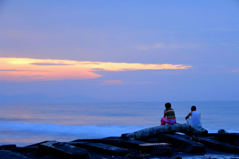 Rear view of men sitting on rock by sea against sky