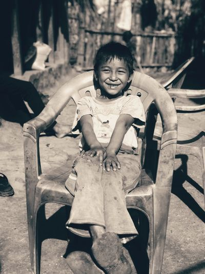 Smiling girl sitting on chair outdoors