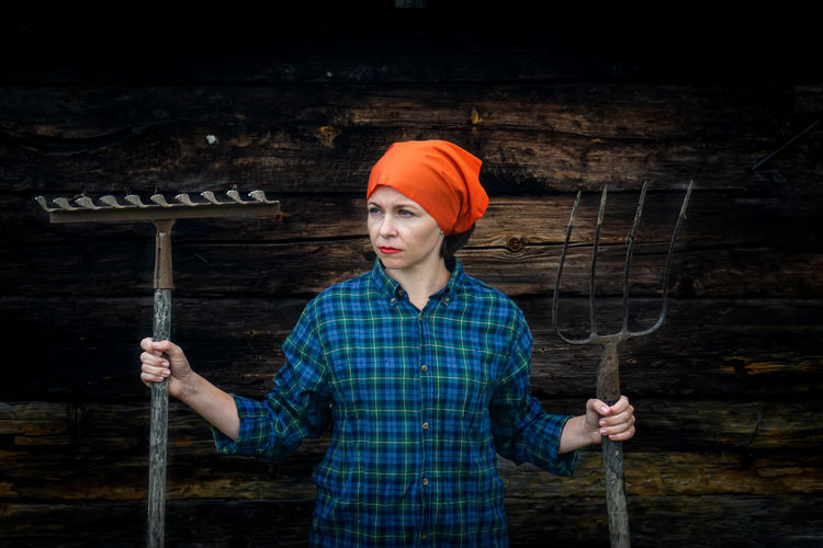Beautiful woman holding gardening equipment while standing against wooden wall