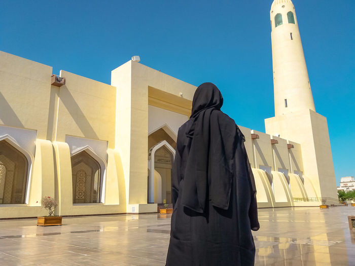Back of woman with abaya dress looking the facade and high minaret of State Grand Mosque in Doha, Qatar, Middle East, Arabian Peninsula. Sunny day with blue sky. Muslim religion concept. Doha Doha,Qatar Qatar Waterfront Woman Model Girl Female Tourist Seascape Tourist Attraction  Holiday Vacation People Mosque Architecture Mosque Door Grand Mosque Islam Islamic Architecture Islamic Muslim Muslim Woman Muslim Culture Arab Religion Built Structure Architecture Belief Spirituality Place Of Worship Building Exterior Building Day Real People Clear Sky Rear View Sunlight Sculpture Sky Nature Blue Outdoors Architectural Column