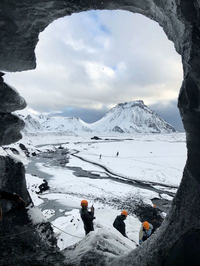 People on snow covered mountain by lake against sky