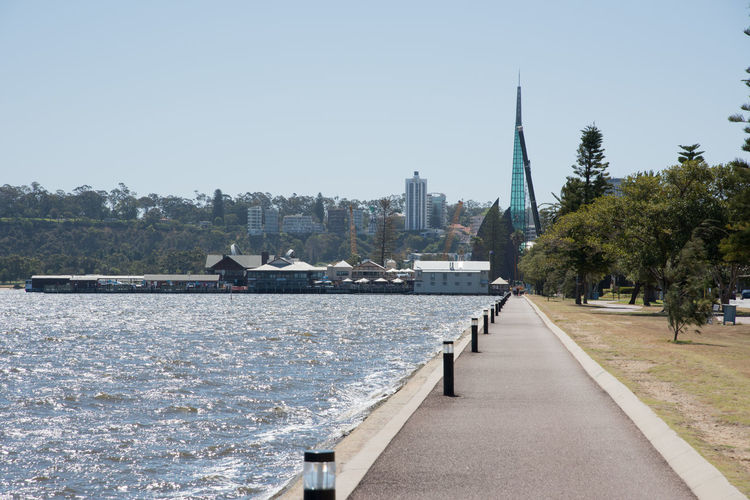 November 17,2016: Swan River with waterfront footpath and Swan Bell Tower view in Perth, Western Australia. Architecture Bell Tower Built Structure City Clear Sky Day Diminishing Perspective Footpath Foreshore Nature Outdoors Path Pedestrian Perth Real People River Sky Swan Bell Tower Swan River Tourism Tower Travel Destinations Water Waterfront Western Australia