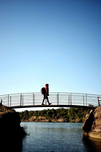 Side View Of Man Walking On Footbridge Over River Against Clear Sky