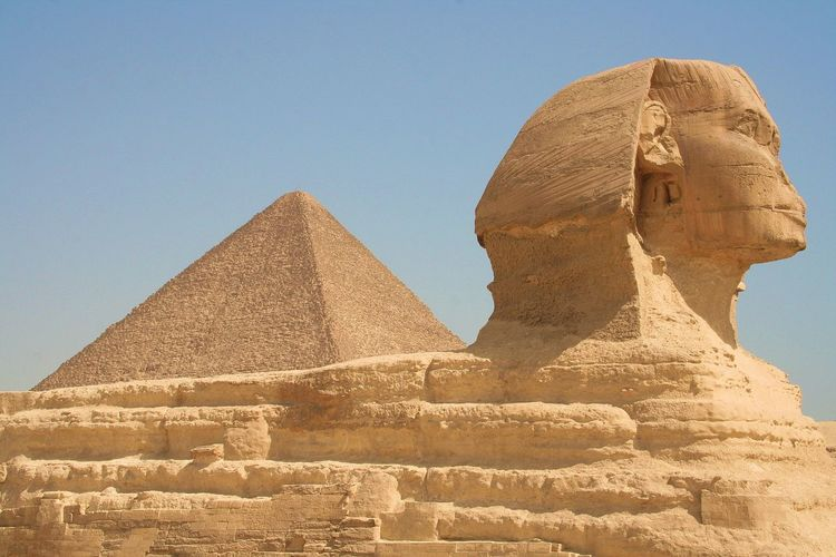 Great sphinx and pyramid against clear sky