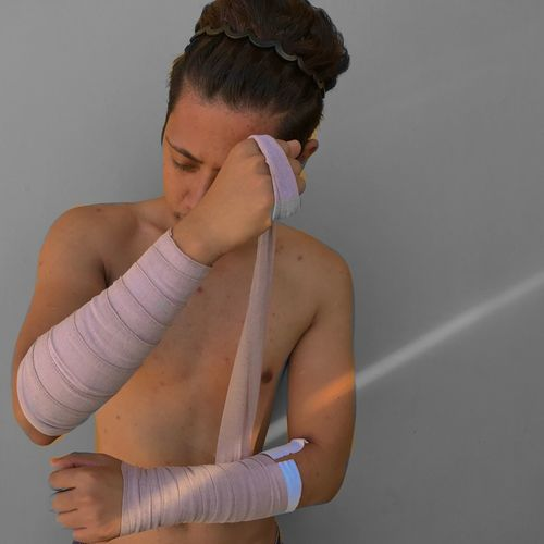Shirtless Young Man Tying Bandage While Standing Against Wall