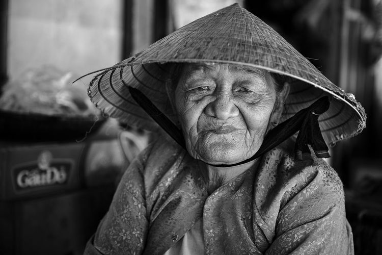 Close-up portrait of woman wearing asian style conical hat