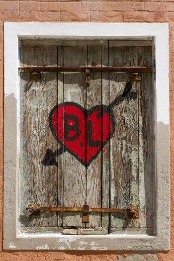 Heart shape hanging on window of old building