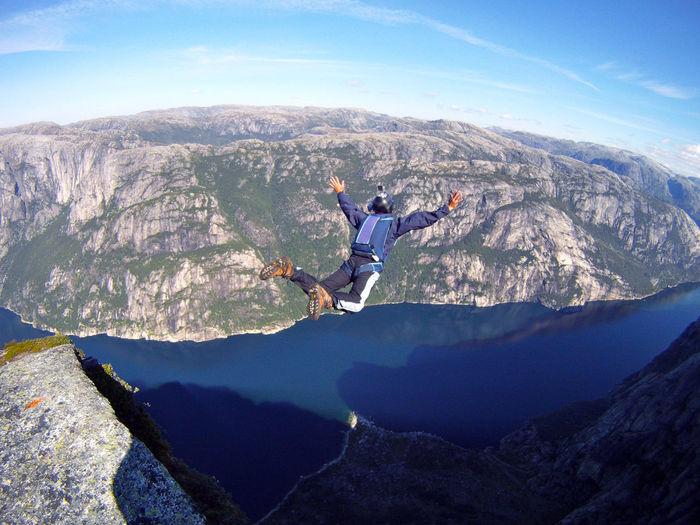 Man base jumping off mountain