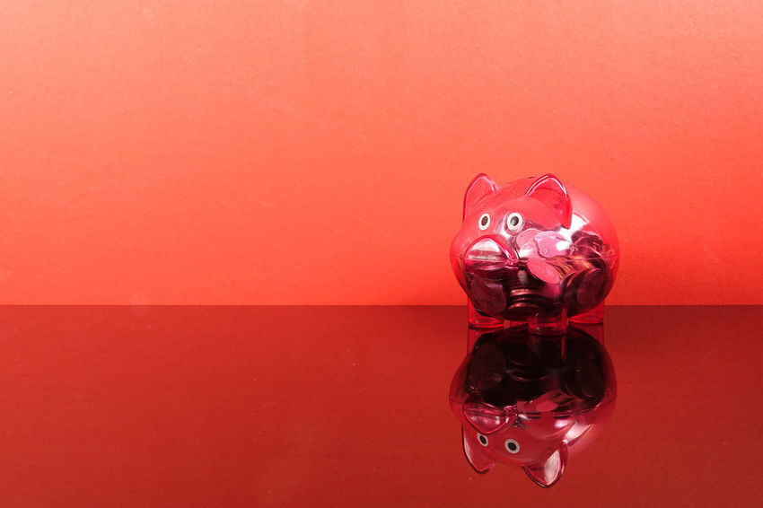 Saving concept with red piggy bank on red background. Piggy Bank Animal Representation Close-up Coin Colored Background Conceptual Photography  Copy Space Glass - Material Indoors  Investment No People Orange Color Pink Background Red Red Background Representation Saving Concept Shape Shiny Single Object Still Life Studio Shot Table Transparent Wall - Building Feature