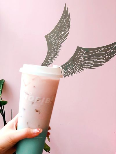 Close-up of hand holding drink against pink wall