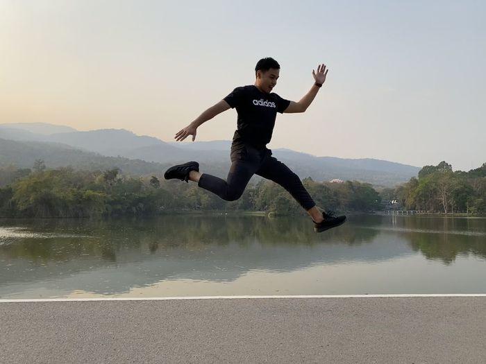 Full length of man jumping in lake against sky